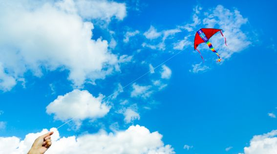 bigstock-Hand-holding-kite-in-the-cloud-102201557