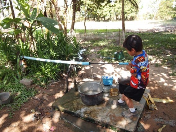 Cambodia with kids trip - Drawing water from well
